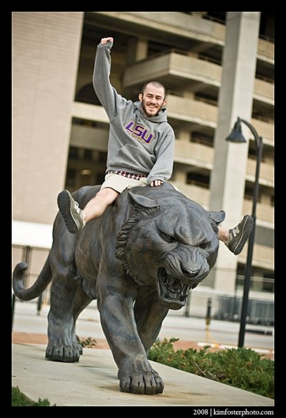 Daily Reveille editor in chief Nicholas Persac rides a bronze tiger.  He later put the paper to bed.